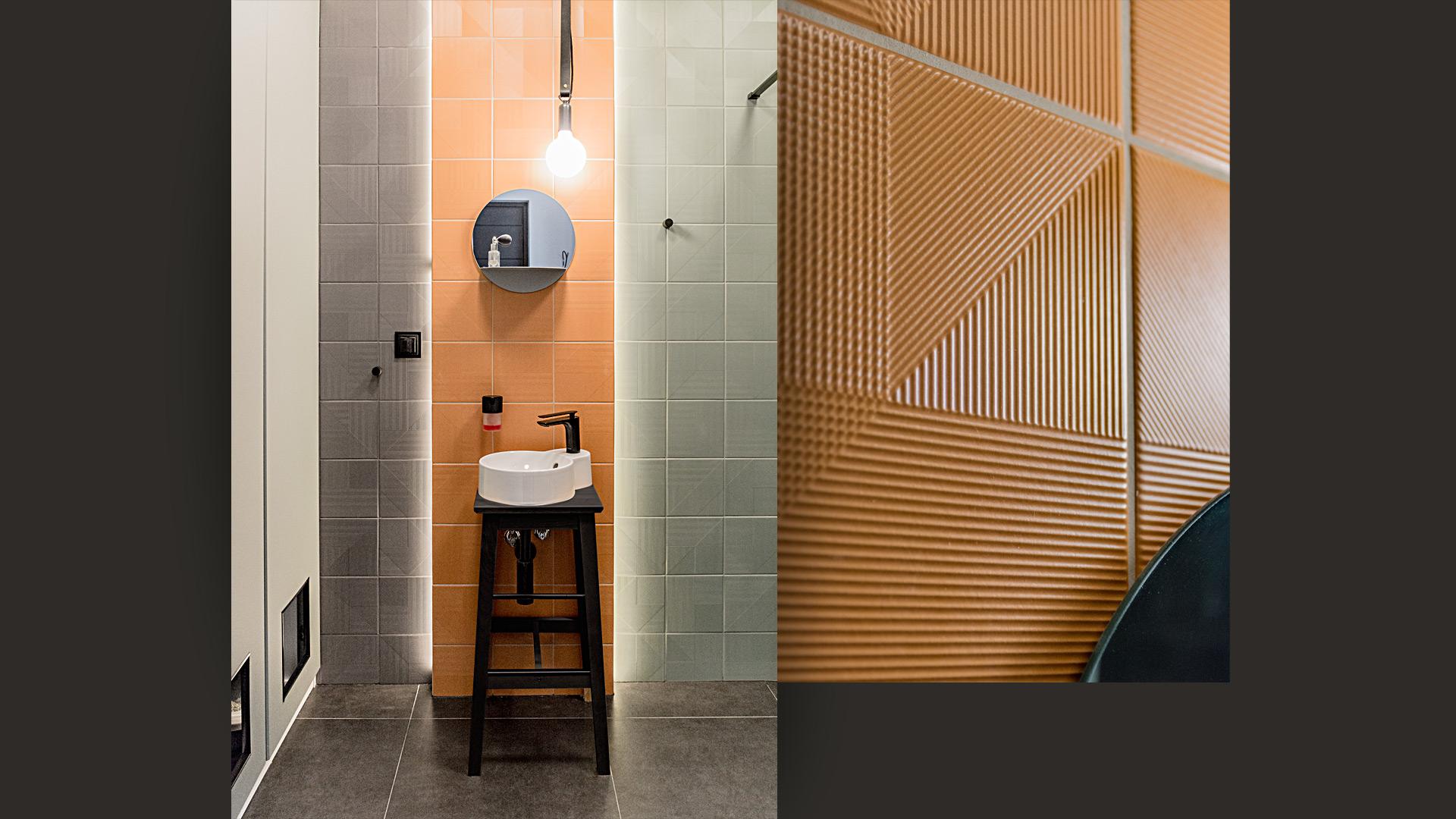 Łazienka na parterze: centralnie wyeksponowana umywalka stoi na lakierowanym na czarno stołku. W szafie gospodarczej ukryto dwie kocie kuwety, do których prowadzą otwory we froncie.