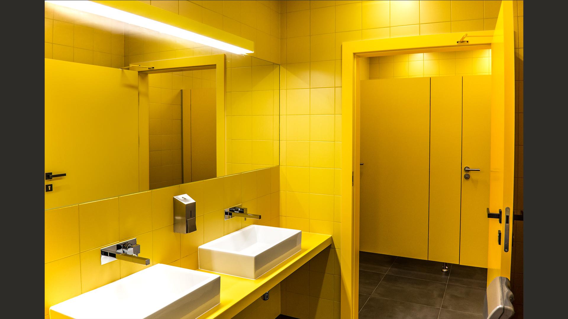 Prosty zabieg konsekwentnego użycia jednego koloru sprawił, że – przy niewielkim budżecie realizacyjnym – powstało bardzo wyraziste wnętrze. Na zdjęciu – damskie toalety.