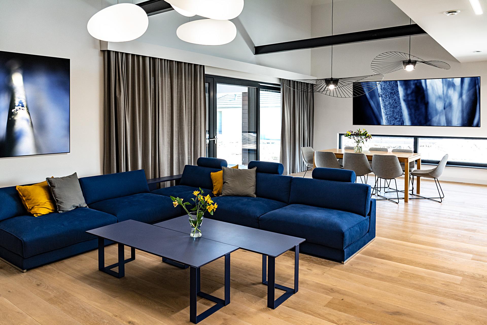Dużą powierzchnię salonu oświetlają lampy dekoracyjne i oprawy techniczne w suficie pod antresolą.