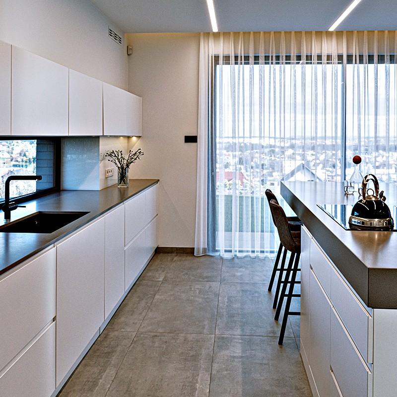 Kompleksowy projekt wnętrz pokaźnej podmiejskiej nieruchomości z dużą ilością okien. Parter na planie otwartym z unikalnymi meblami, których solidne blaty sprawiają wrażenie lewitujących w powietrzu.