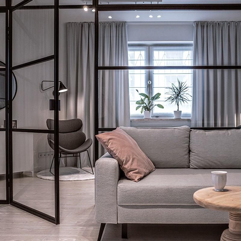 Przeszkolona metalowa ściana działowa w stylu industrialnym pomaga w odnowionym układzie funkcjonalnym apartamentu, na łączeniu salonu i sypialni