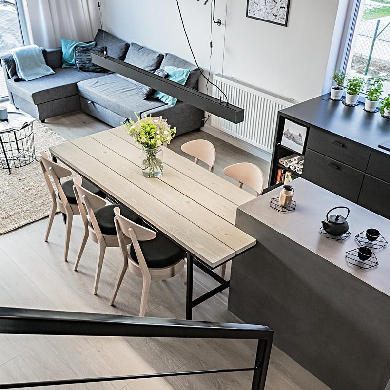 Wnętrze wygodnego i jasnego domu, w którym dominuje bielone drewno i czarne, graficzne dodatki.